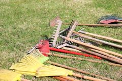 Rakes, shovels, brooms and brushes, household inventory for cleaning, arrangement of territory, digging of the earth lie on the gr royalty free stock photos