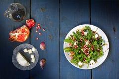 Raketsalade met kaas en granaatappel op rustiek hout, mening Fr Stock Foto