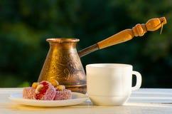 Rakhat lokum、Cezve和一个杯子咖啡在阳光下,在绿叶背景  库存图片