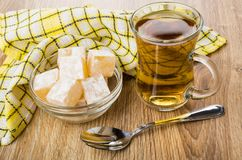 Rakhat-lukum in bowl, cup of tea, napkin and teaspoon. Rakhat-lukum in transparent bowl, cup of tea, napkin and teaspoon on wooden table Royalty Free Stock Image