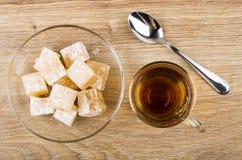 Rakhat-lukum in transparent saucer, cup of tea and teaspoon. Heap of rakhat-lukum in transparent saucer, cup of tea and teaspoon on wooden table. Top view Stock Photo