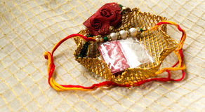 Rakhi thread in gold holder with tika & rice Royalty Free Stock Photography