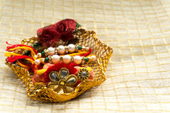 Rakhi thread in gold holder with tika & rice Stock Image