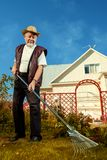 Care about lawn. Raking in the garden. Happy senior man gardening in retirement stock photography