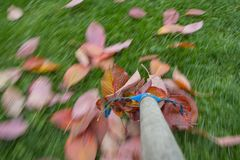 Raking leaves. Autumn work in the garden - long exposure time - accentuating movement in the photo stock image