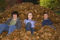 Raking Leaves Three Teens Sitting in Leaf Pile. Three teens relaxing in a leaf pile after raking leaves royalty free stock images
