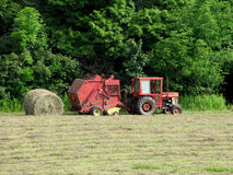 Raking Rolls of Hay. Tractor and machine for raking. rolling and tying the cut hay Stock Photo