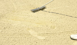 Raking the sand in the bunker Stock Photos