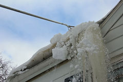 Raking the snow off of a roof Royalty Free Stock Photo