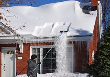 Raking Snow off the Roof. Man uses a roof rake to remove snow from the roof Royalty Free Stock Images