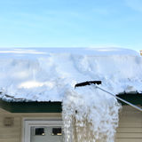 Raking snow from roof Stock Photos