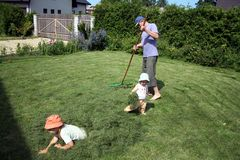 Raking up in the court. A father and two little daughters raking up the cut grass in the court of their house Royalty Free Stock Image