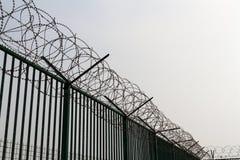 Rakknivtråd överst av det gröna staketet som bevakar den franska färjaterminalen Arkivbilder