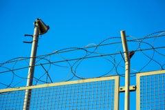 Rakknivtråd försåg med en hulling - binda överkanten av säkerhetsstaketet Royaltyfri Fotografi