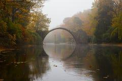 Rakotzbrücke (Devil's bridge) in early morning mist. Rakotzbrücke (Devil's bridge) in early morning mist, in autumn, Kromlau, Germany Stock Image