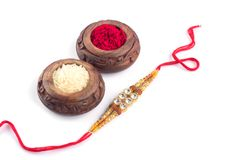 Raksha Bandhan background with an elegant Rakhi, Rice Grains and Kumkum on a white background. A traditional Indian wrist band whi. Raakhi and a gift for the stock images