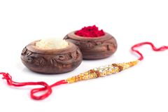 Raksha Bandhan background with an elegant Rakhi, Rice Grains and Kumkum on a white background. A traditional Indian wrist band whi. Raakhi and a gift for the royalty free stock images