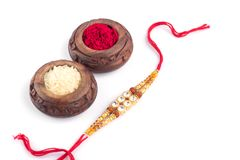 Raksha Bandhan background with an elegant Rakhi, Rice Grains and Kumkum on a white background. A traditional Indian wrist band whi. Raakhi and a gift for the stock image