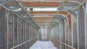 Rakt som in fäktas bur-som bron för den gå banan över mellanstatligt - den mulna dagen för den snöig vintern - cement, och metall arkivfoton
