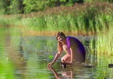 Ralax молодой женщины около озера Стоковое Фото