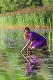 Ralax молодой женщины около озера Стоковое Изображение