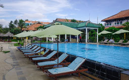Ralaxing chairs at swimming pool of luxury resort. Phan Thiet, Vietnam - Jun 3, 2017. Swimming pool at a luxury resort in Phan Thiet, Vietnam. Phan Thiet belongs Royalty Free Stock Images