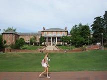 RALEIGH NC/USA - 4-25-2019: En kvinnlig student går på universitetsområde av norr Carolina State University i Raleigh royaltyfri bild