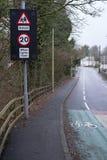 Ralentissement de panneau routier d'école quand les lumières clignotent bâtiment à l'arrière-plan images libres de droits