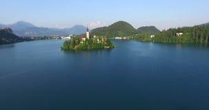 Ralentissez la vue aérienne de peu d'île sur le lac slovène saigné banque de vidéos