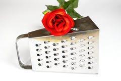 Rallador de la cocina con la rosa del rojo en un fondo blanco Fotos de archivo
