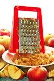 Rallador y manzanas de la cocina imagen de archivo