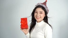 Rallentatore della donna felice con il cappello e la tenuta del contenitore di regalo rosso di natale in un gesto di dare archivi video