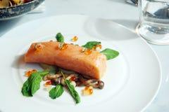 Rallenti il filetto di bue di color salmone cucinato con insalata ed il salmone delle uova sul piatto bianco Fotografie Stock