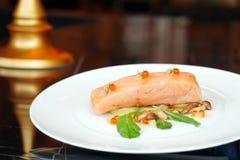 Rallenti il filetto di bue di color salmone cucinato con insalata ed il salmone delle uova sul piatto bianco Fotografie Stock Libere da Diritti
