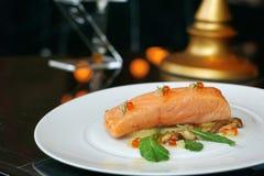 Rallenti il filetto di bue di color salmone cucinato con insalata ed il salmone delle uova sul piatto bianco Fotografia Stock