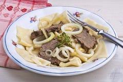 Rallenti la carne di cavallo cotta con le tagliatelle, il piatto kazako Beshbarmak Immagine Stock