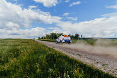 Rally car driving on a dust road in green grass and blue sky Royalty Free Stock Image