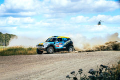Rally car driving on a dusty road above him flies a helicopter Royalty Free Stock Photography