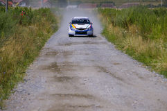 Rally car on gravel road. Front view with village houses in background Stock Photos