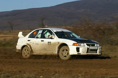 Rally car - Mitsubishi EVO VI. A rally race car - Mitsubishi EVO 6 - on a muddy gravel track.Without logos royalty free stock images