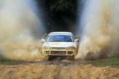 Rally car splashing water on dirt road. Stock Image