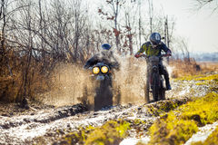 Rally motorbike rider is ahead of another on a dirt road. With deep mud Royalty Free Stock Photography