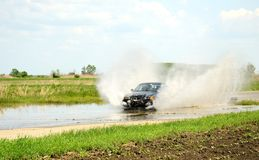 Rally race in Kunmadaras, Hungary April 27. BMW driving over the large puddle. Stock Photo