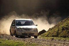 Rally racing on dust gravel. Santa, Sibiu, Romania - October 20, 2012: White Dacia Logan competing in the Sibiu - Santa Rally Show, Romania. Dust is thown all royalty free stock images