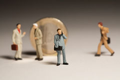 Rallying Around The Euro. Miniture, model businessmen standing around an upright euro coin in consultation and discussion Royalty Free Stock Image