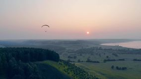 Ram-air parachute is drifting in the sky while the sun is setting