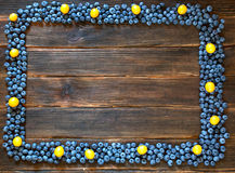 Ram av blåbäret och körsbär-plommonet på mörk träbakgrund Arkivbild