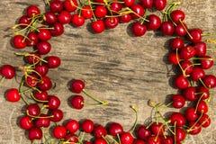 Ram av den röda körsbäret på träbakgrund Royaltyfri Fotografi