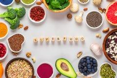 Ram av det rena ätavalet för superfood: frukt grönsak, frö, superfood, muttrar, bär på vitmarmorbakgrund arkivfoto