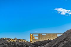 Ram av ett oavslutat hus bak en kulle av jord p? en konstruktionsplats arkivbild